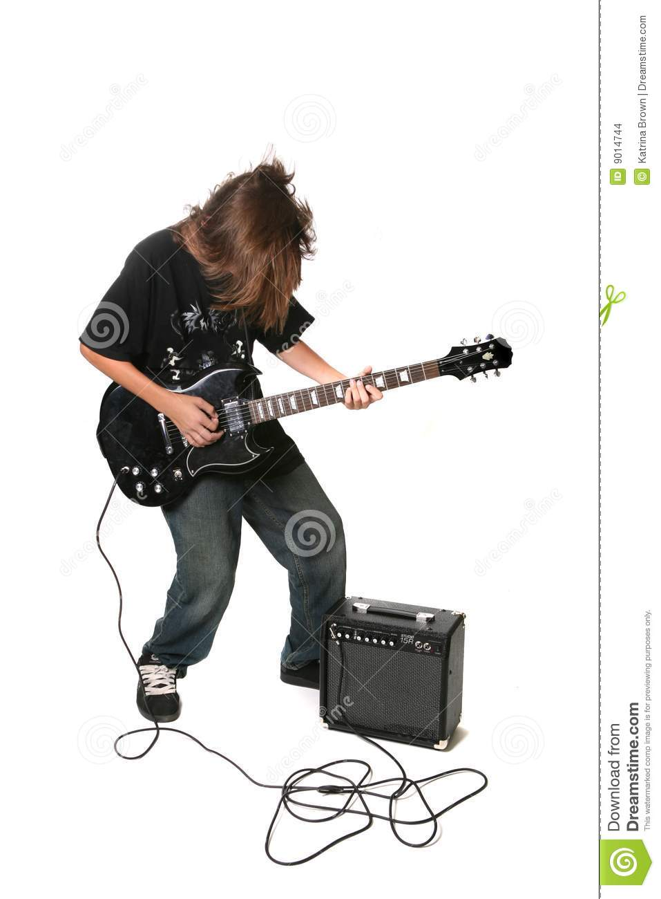 teenager playing electric guitar with amplifier stock