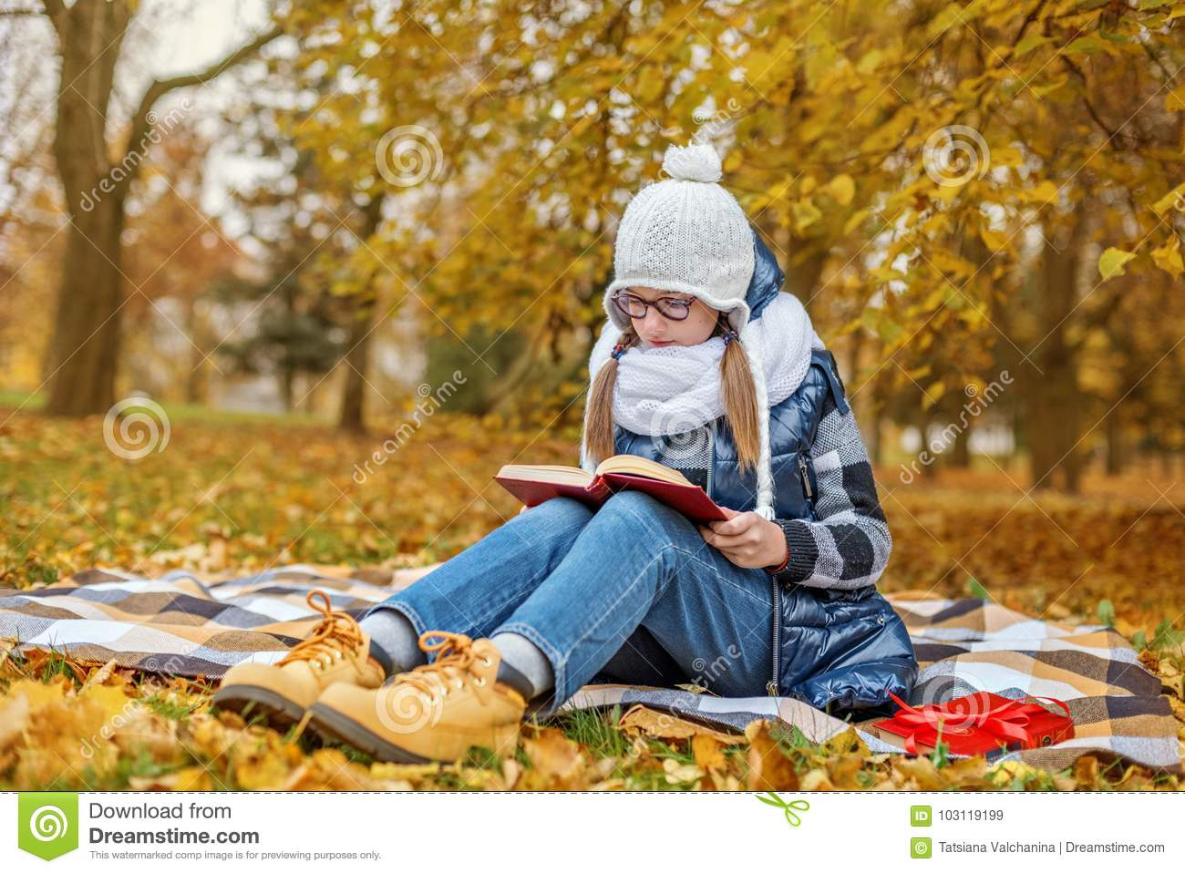 Teenager pupil girl in glasses studies textbook in the park sits on a plaid in a cozy white scarf and hat
