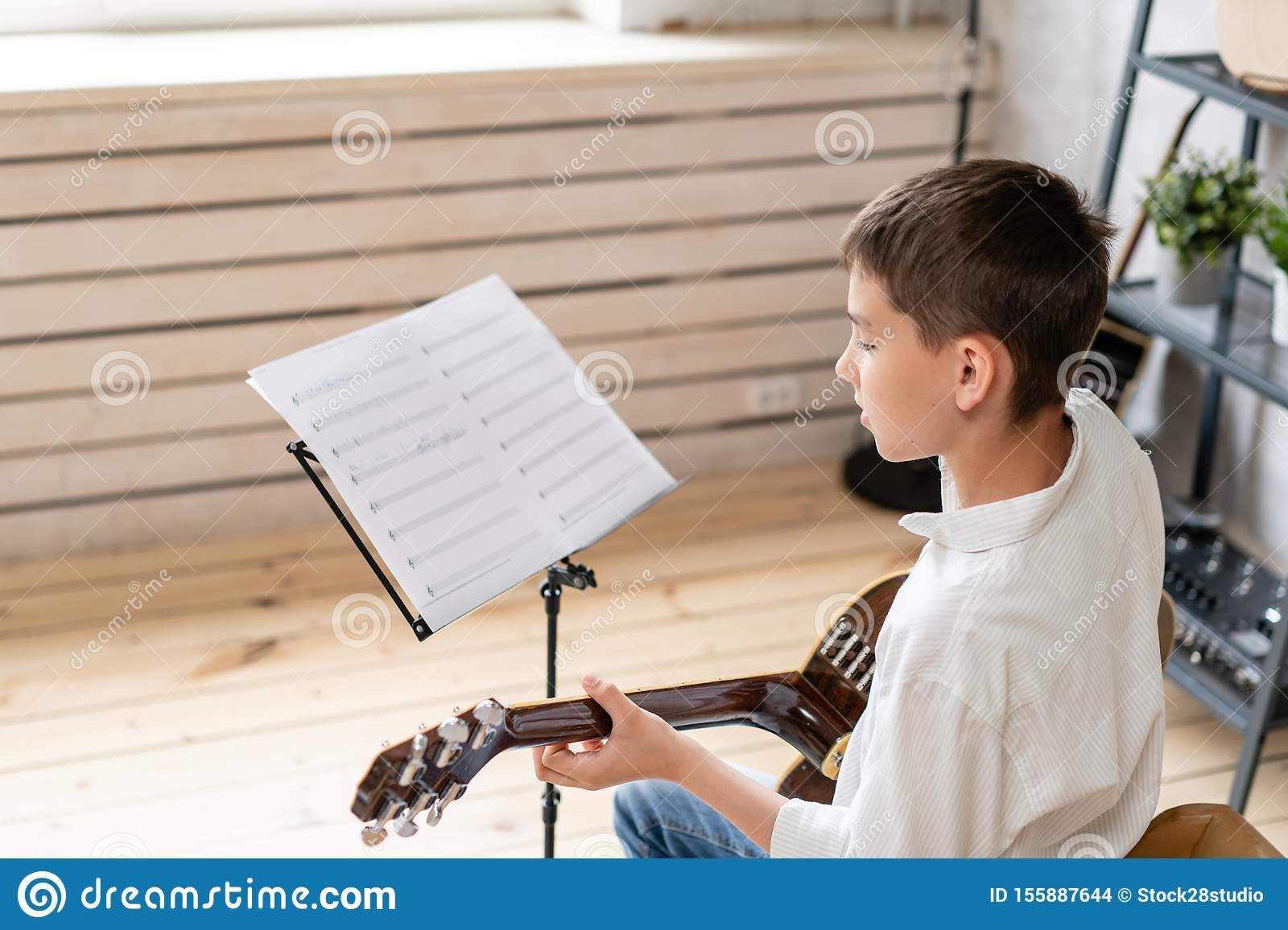 Teenager sits in chair behind sheet music and learning new melody for acoustic guitar