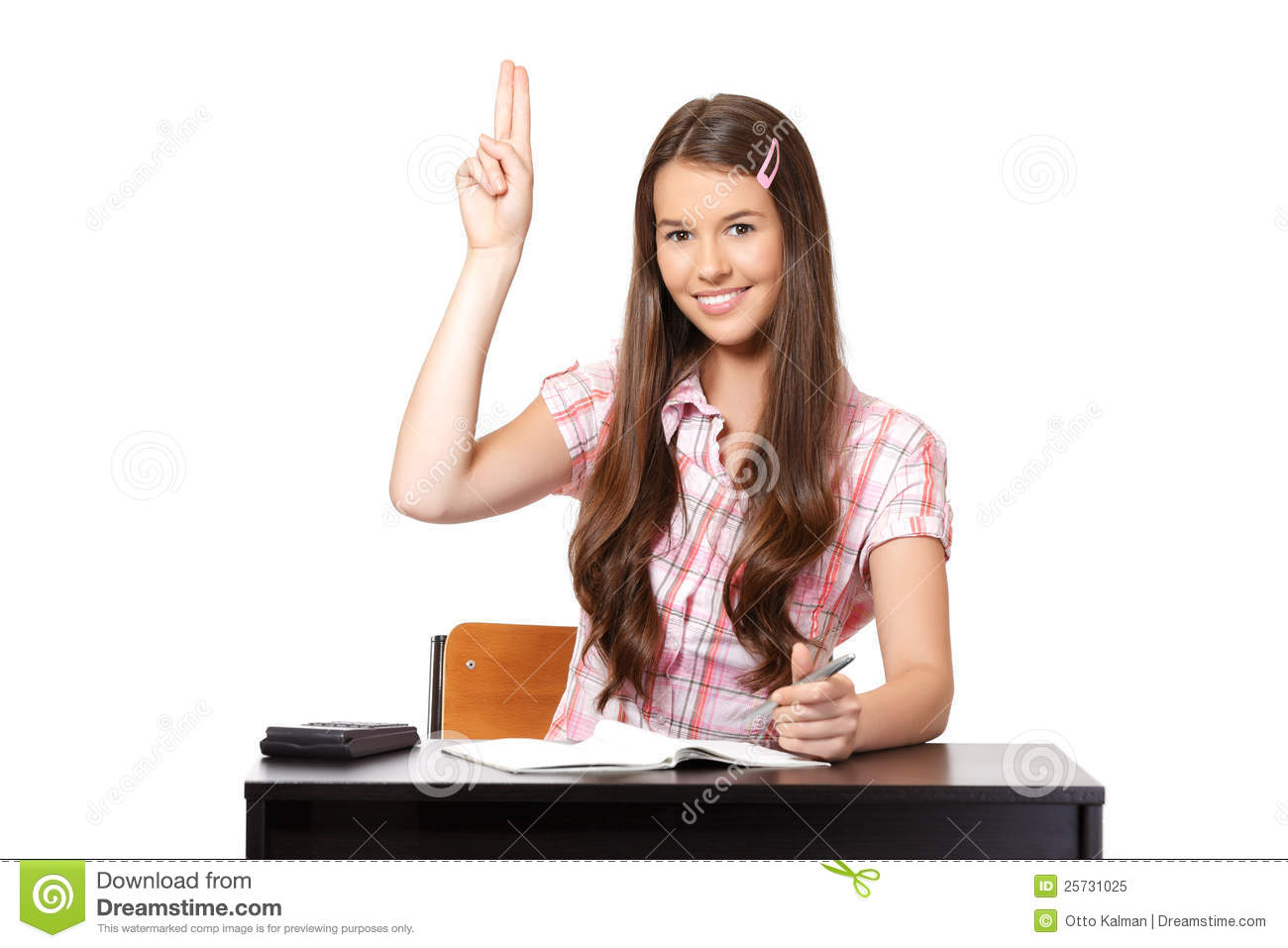 Teenager sitting in classroom with raisedhand
