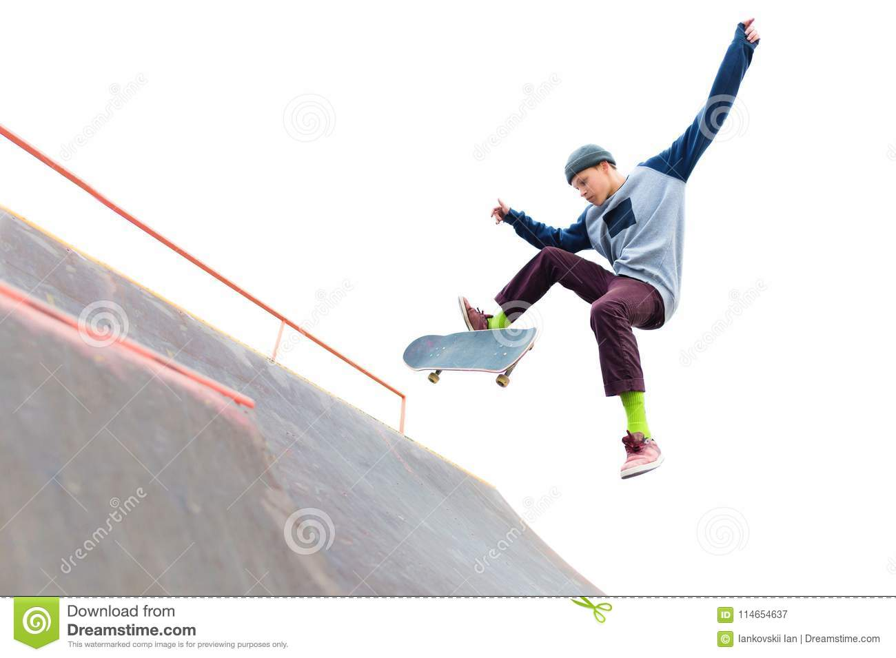 The teenager skateboarder in the cap does a trick with a jump on the ramp in the skatepark. skater and ramp on