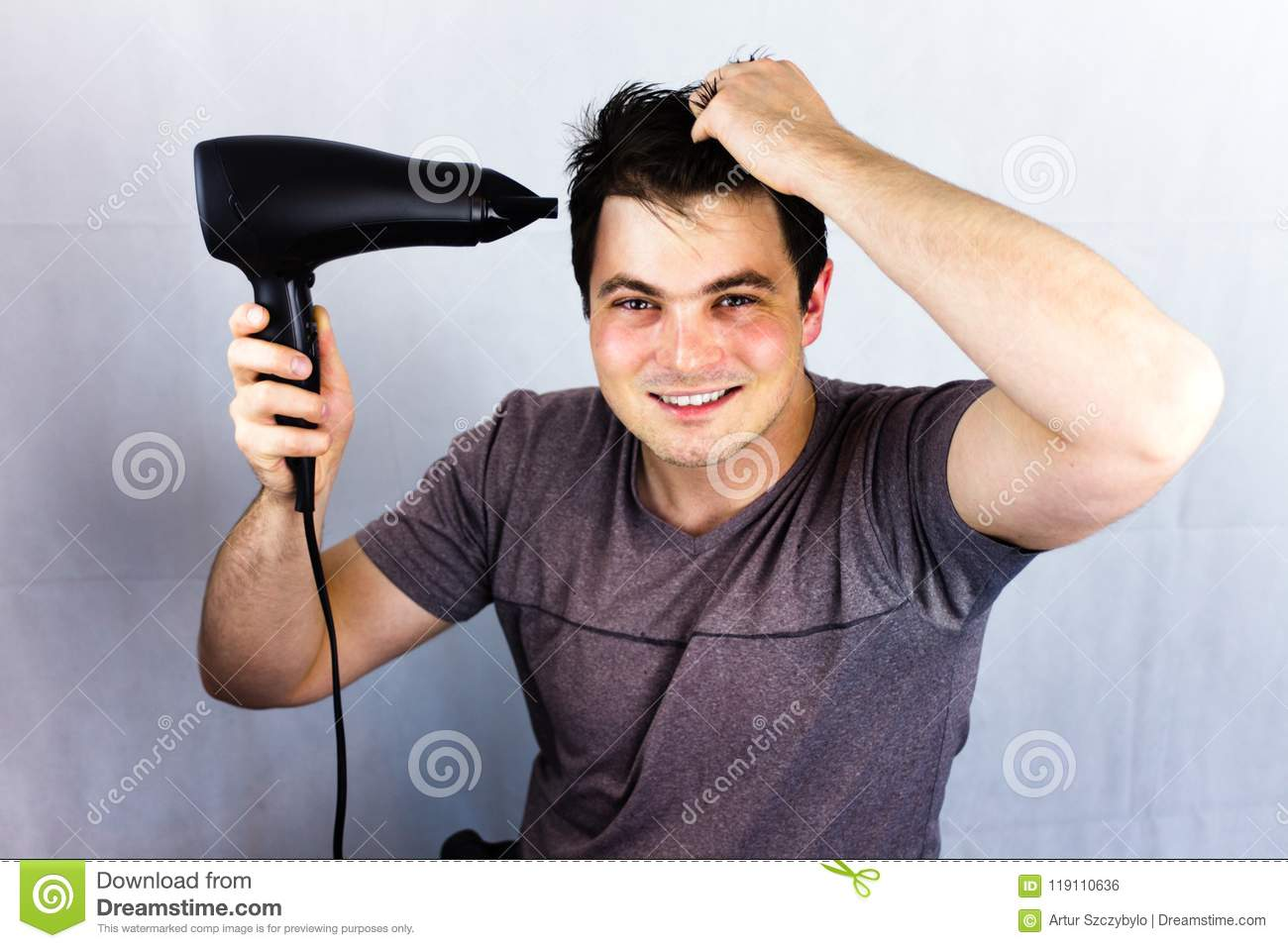 Teenager smiling while he dries his hair. Man holding hair blower. Young man dries hair with an electric fan. Preparing a haircut