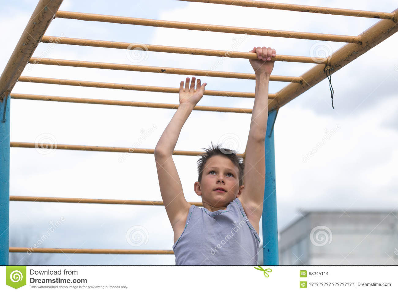 A teenager in a T-shirt is engaged in gymnastics on a horizontal bar
