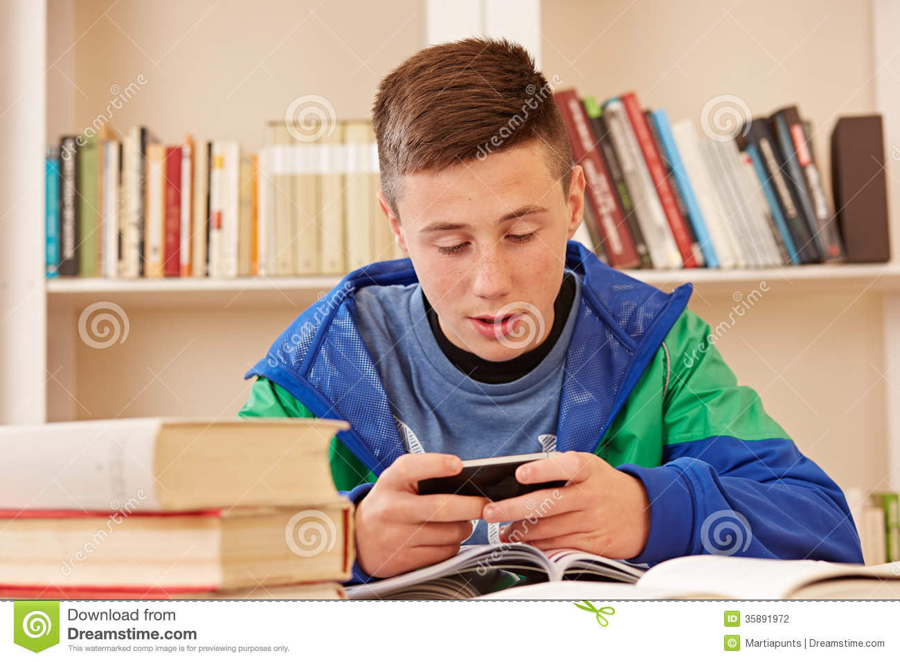 Teenager Texting With Smartphone While Studying Stock