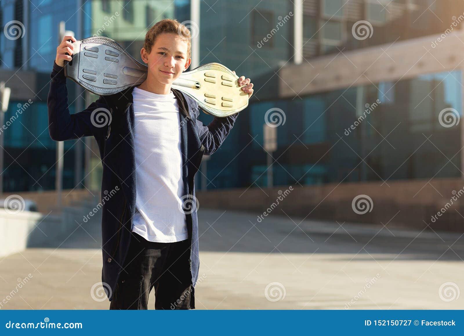 Teenagerholdingskateboard draußen, stehend auf der Straße und betrachten Kamera Kopieren Sie Platz