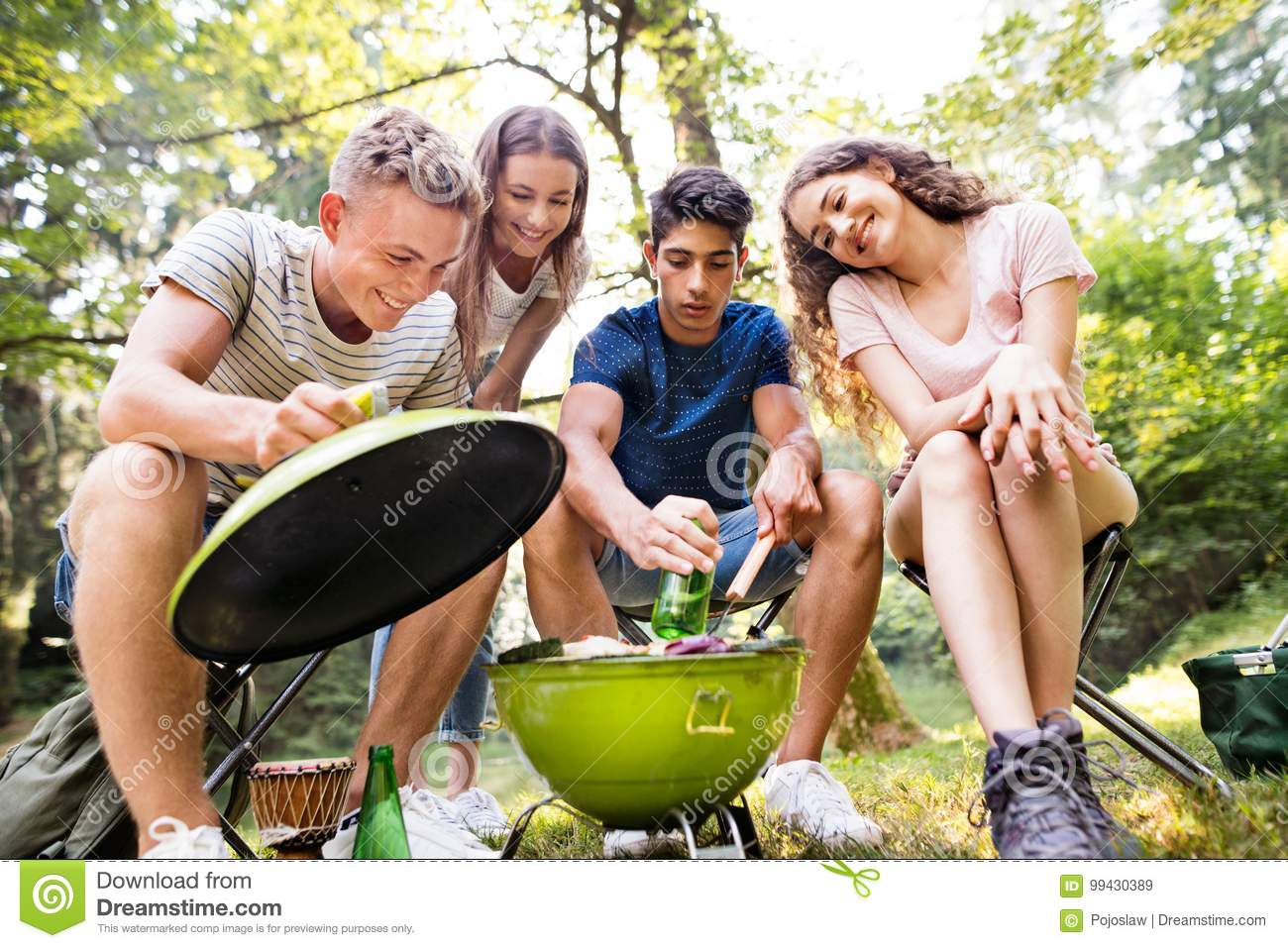 Teenagers camping, cooking meat on barbecue grill.