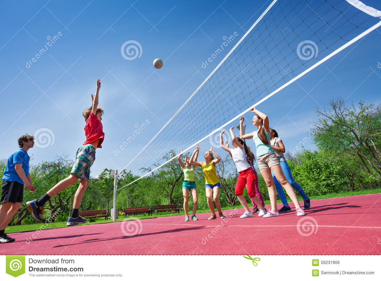 teenagers play volleyball game on playing ground stock photo