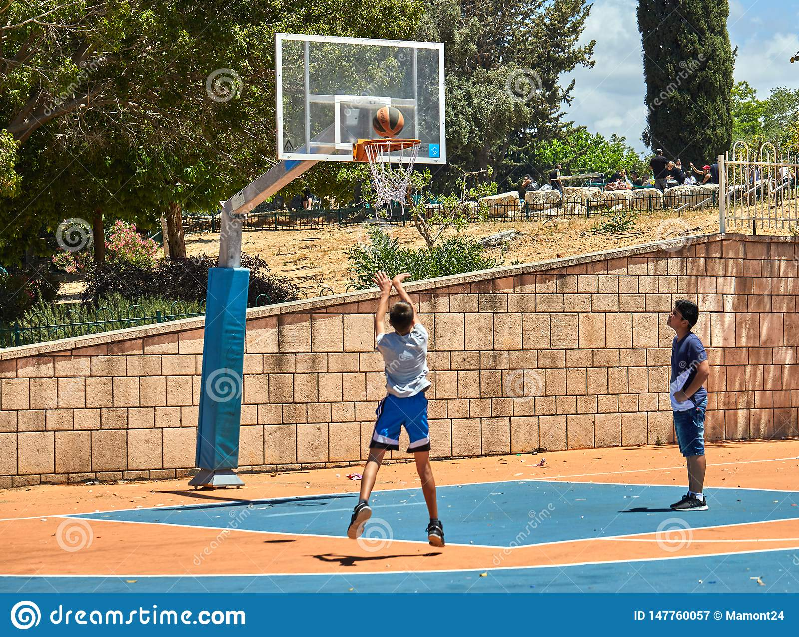 Teenagers playing basketball in a city park