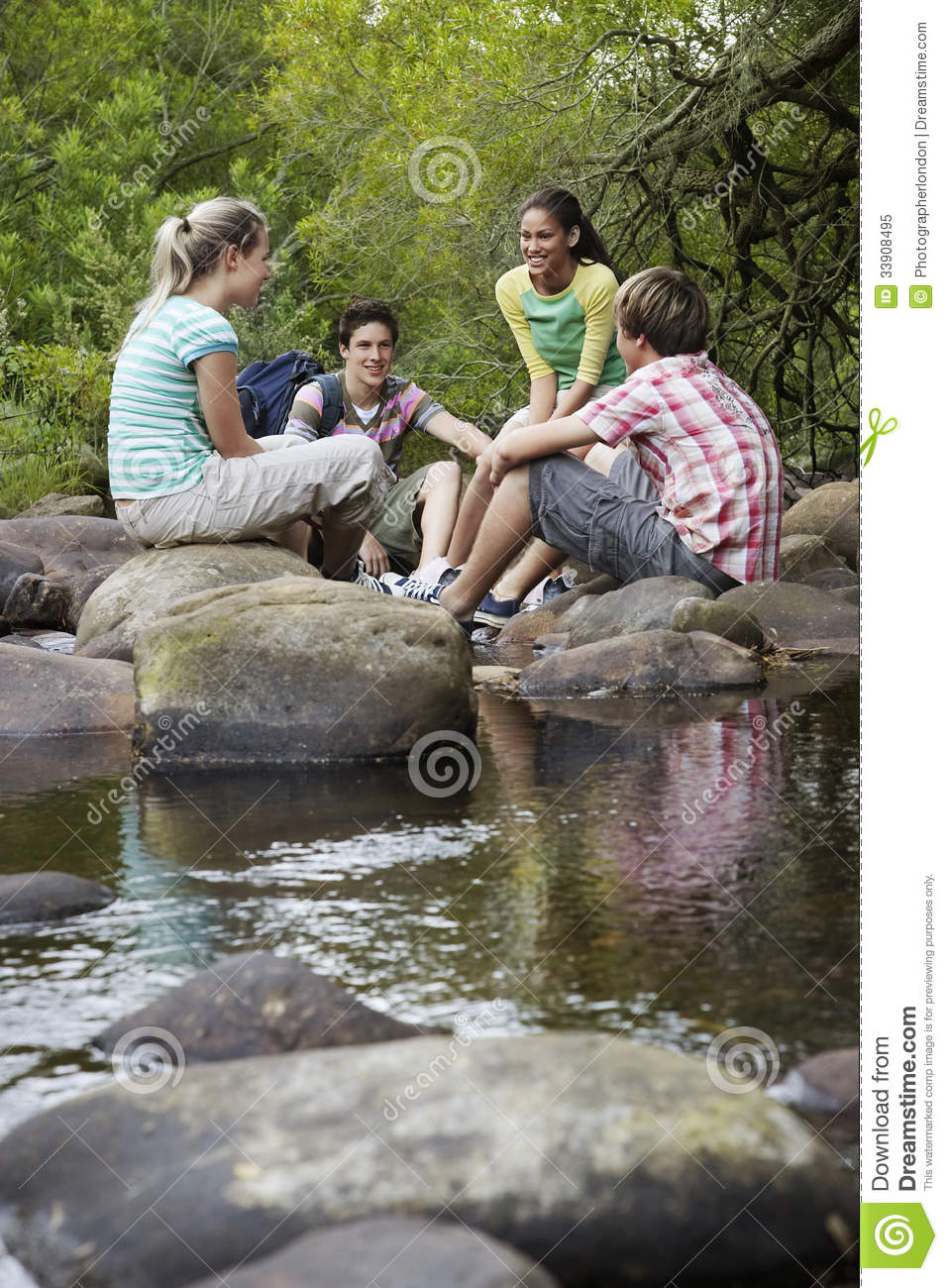 Teenagers Sitting On Stones By River In Forest Royalty