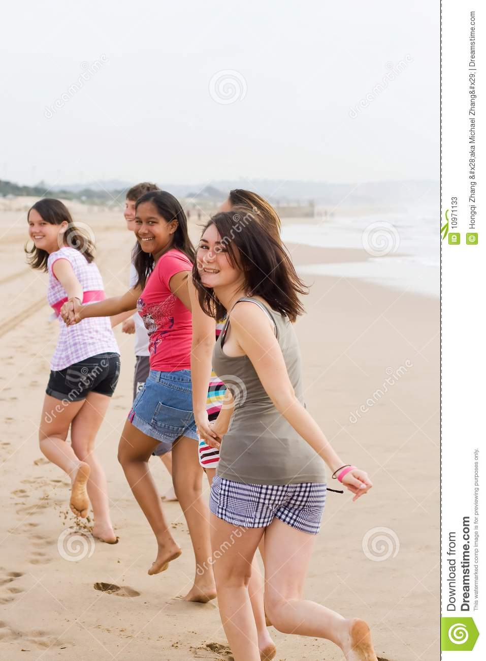 Young group of teens running on beach and having fun