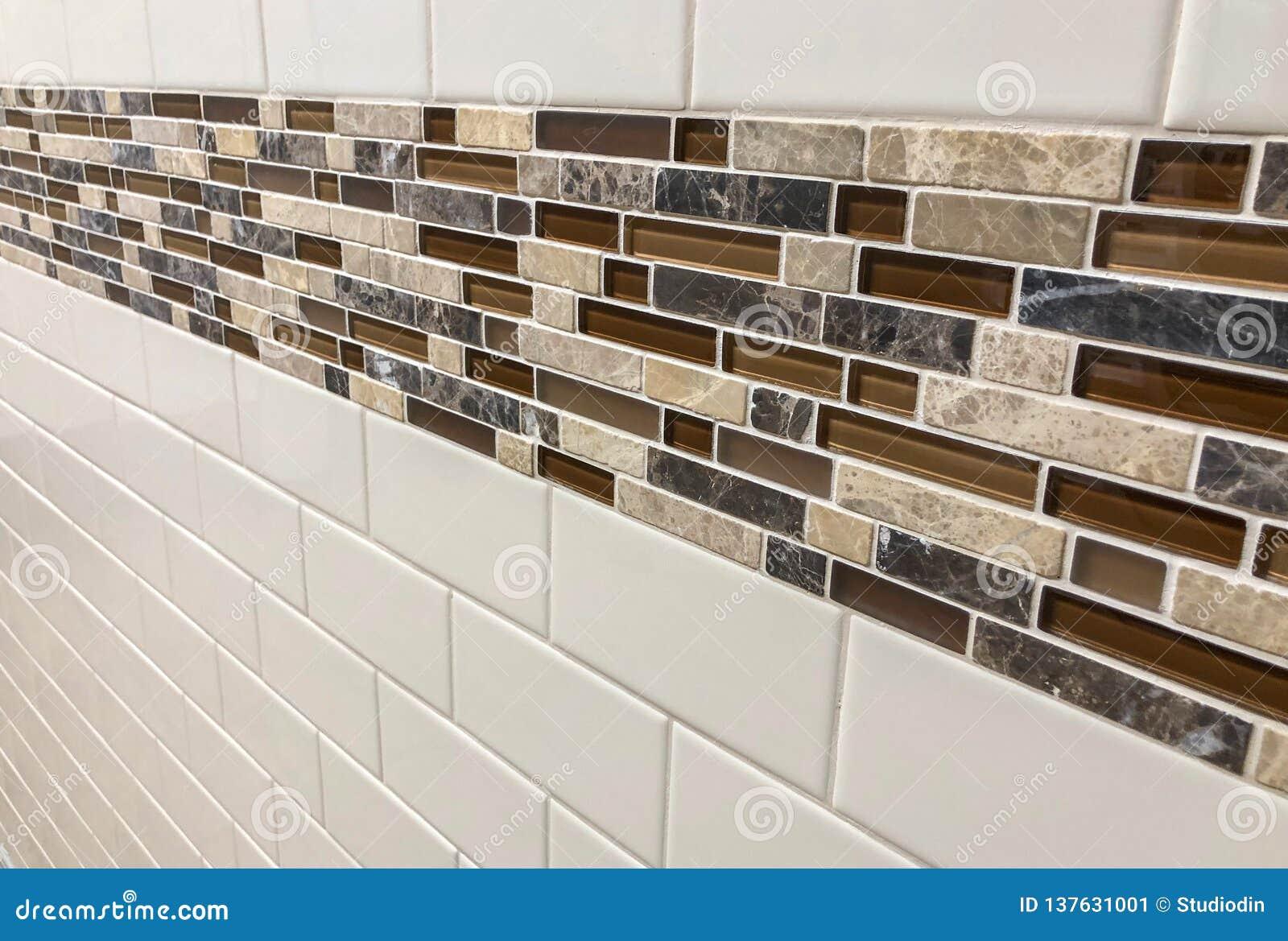 Tegelplattor som göras av exponeringsglas och stenen som installeras på väggen som garnering- eller kökbacksplash