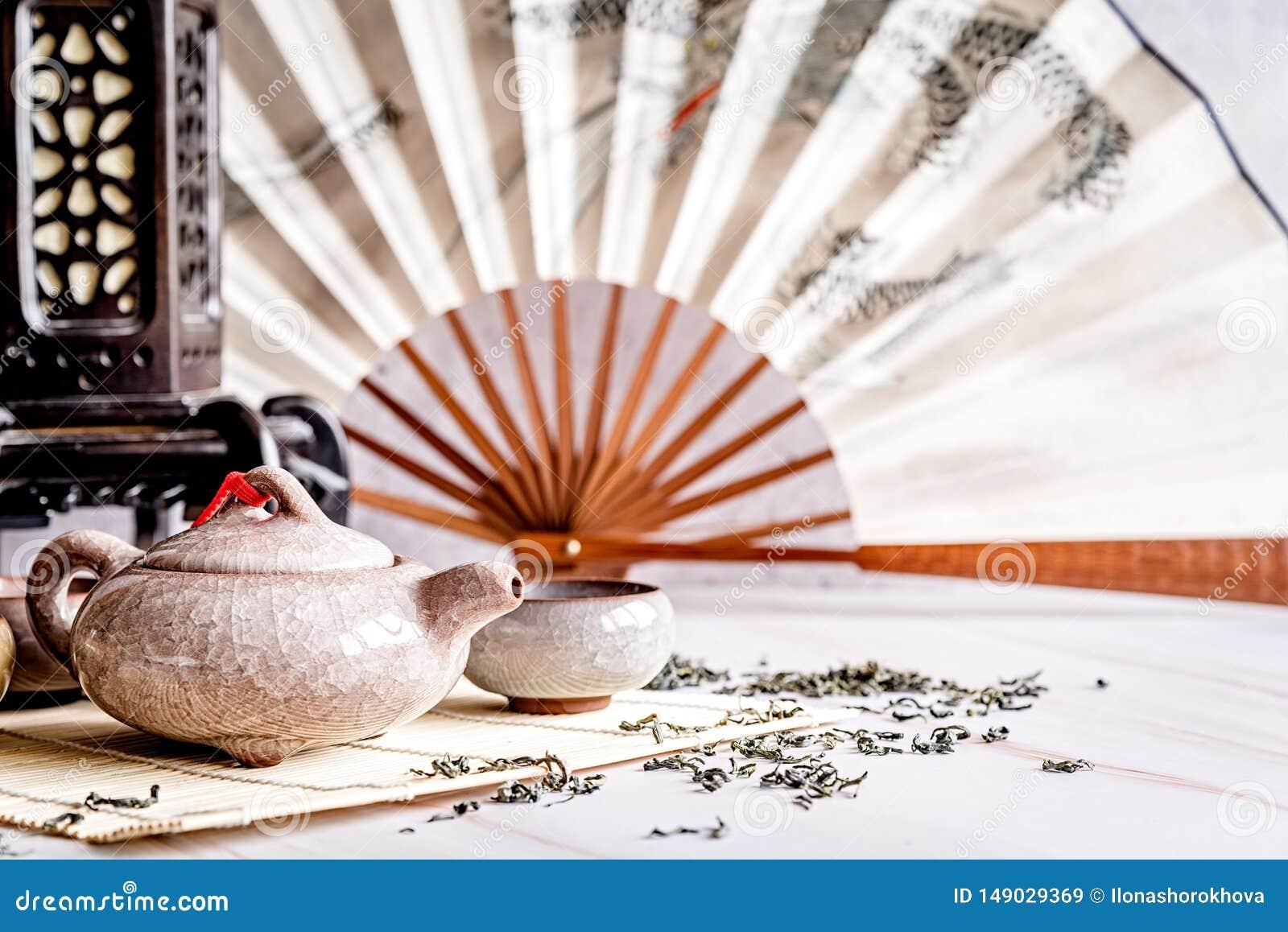 Teiera asiatica con i tazza da the su tablamat di bambù decorato con il fan cinese, la lanterna ed il tè verde sparso su marmo bi