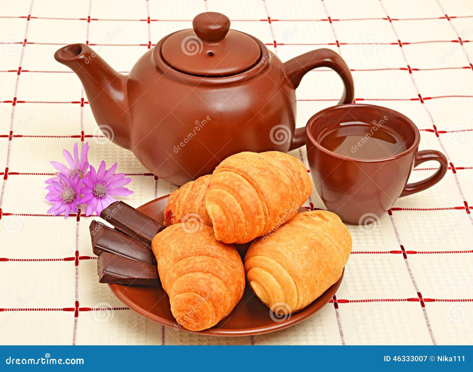 Teiera, tazza e sauser di Brown con il croissant