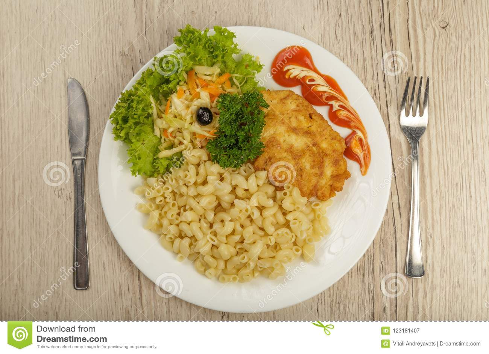Teigwaren mit einem Stück gegrilltem Fleisch und Salat
