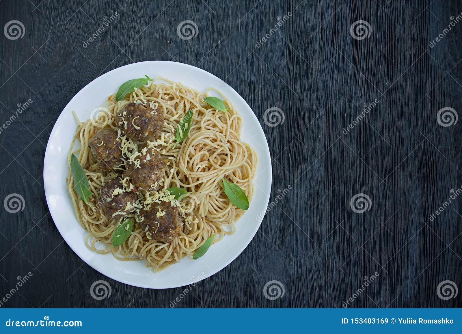 Teigwaren mit Fleischklöschen und Petersilie in der Tomatensauce Dunkler h?lzerner Hintergrund Ansicht von oben