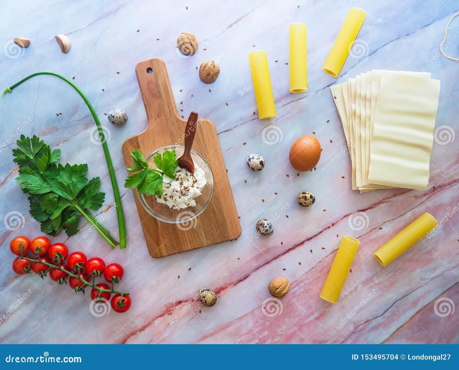 Teigwaren und Lasagne Cannoli, die Konzept kochen Bestandteile auf einer Marmoroberfläche mit einem hölzernen Schneidebrett