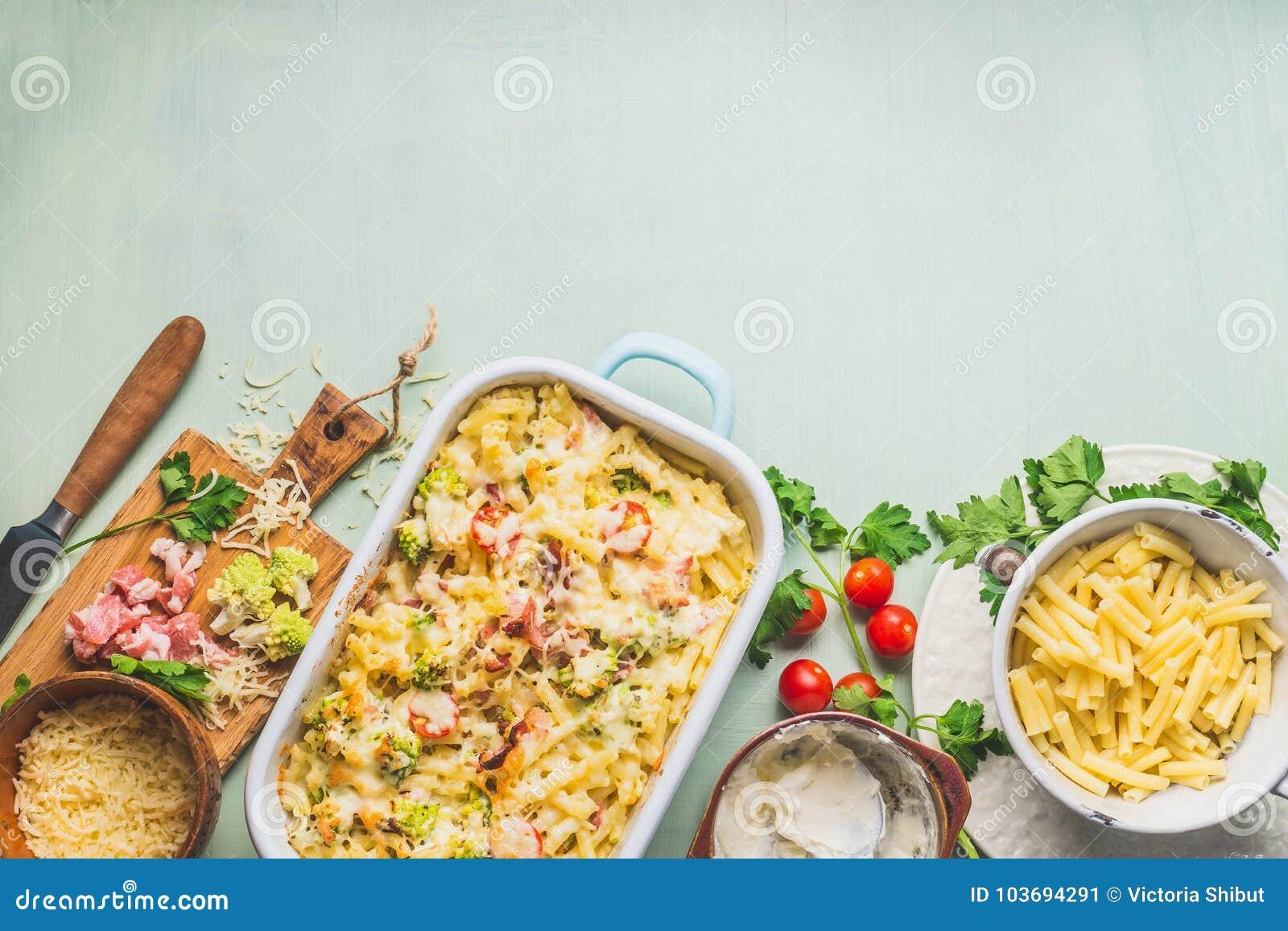 Teigwarenkasserolle mit romanesco Kohl und Schinken in der sahnigen Soße, auf Küchentischhintergrund mit Bestandteilen, Draufsich