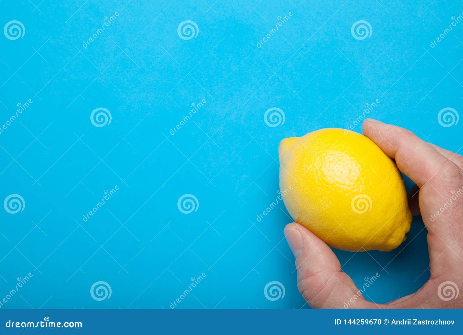 Teil Vitamine in der hand- gelben Zitrone auf einem blauen Hintergrund