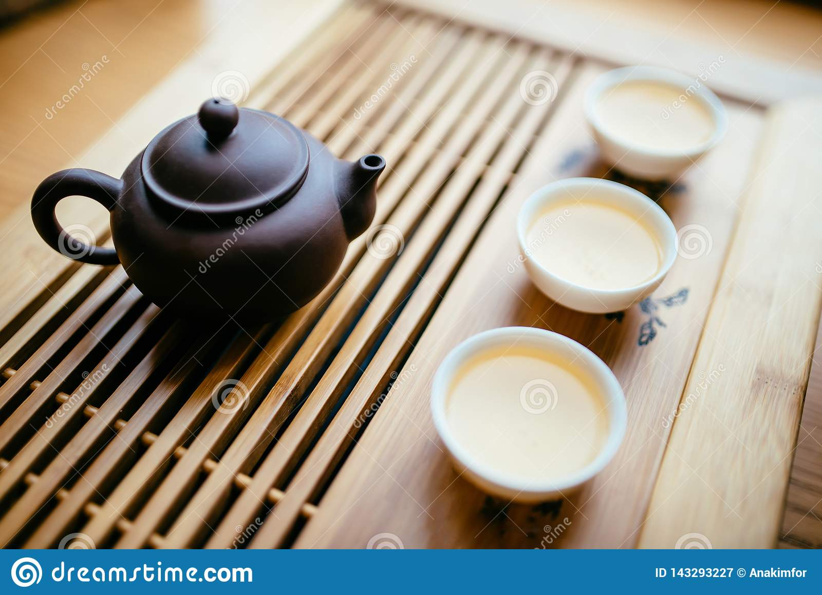 Tekanna och koppar med kinesiskt te på tabellen för teceremonin