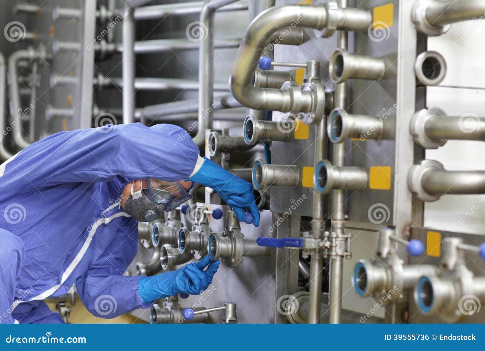 Tekniker i overaller som underhåller det teknologiska systemet i växt