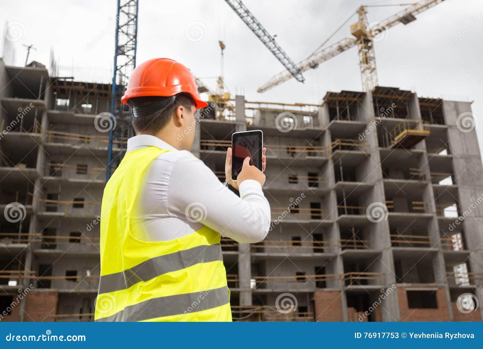 Tekniker på byggnadsplats med den digitala minnestavlan