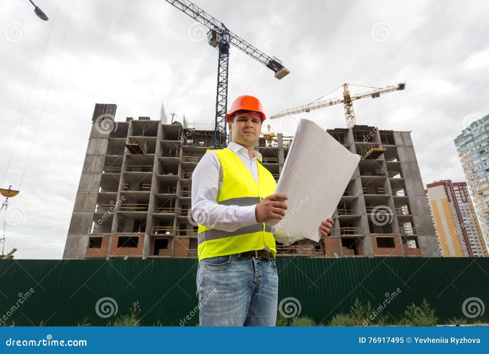 Tekniker på byggnadsplats med ritningar