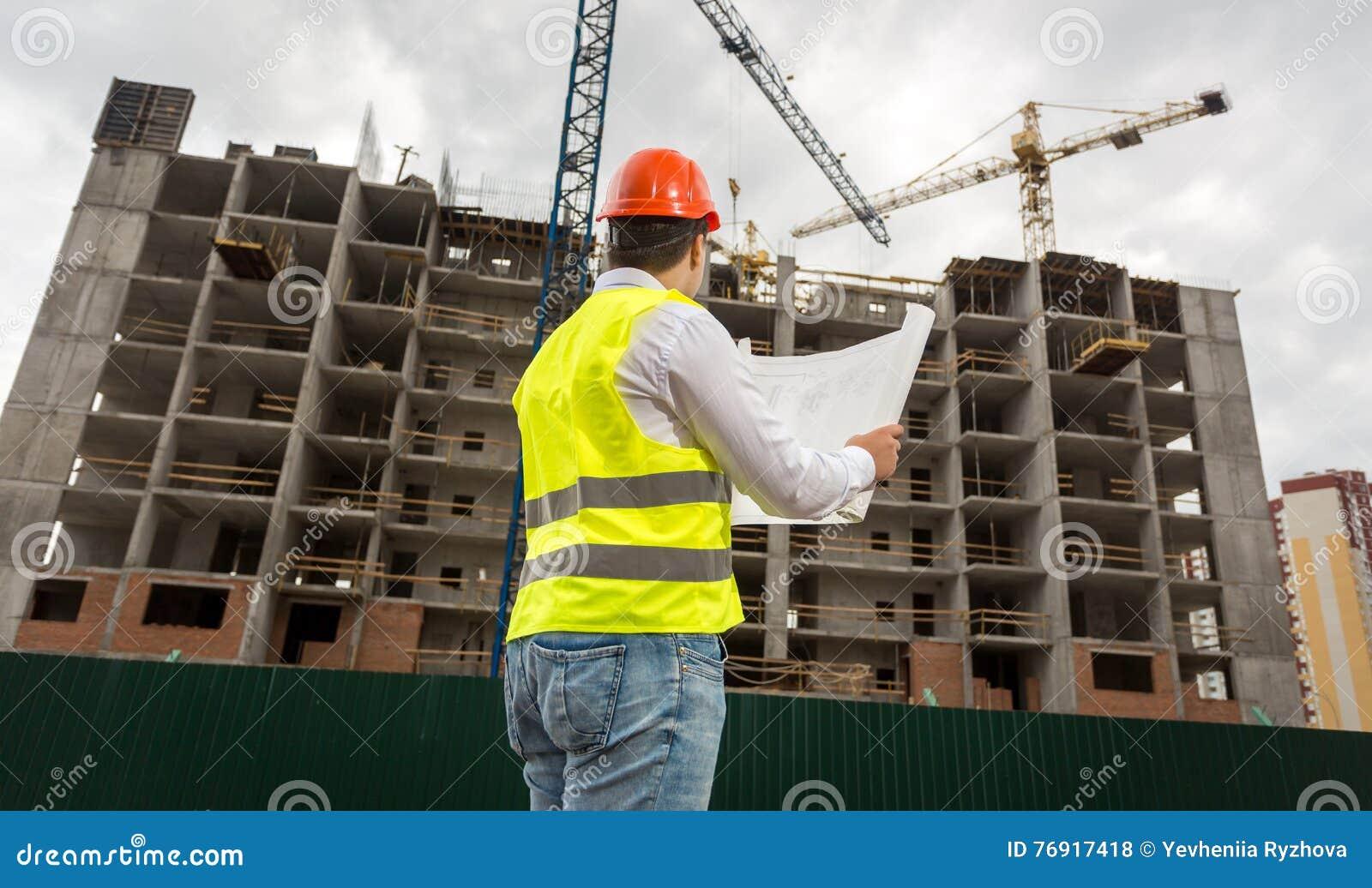 Tekniker på byggnadsplats som kontrollerar plan och ritningar