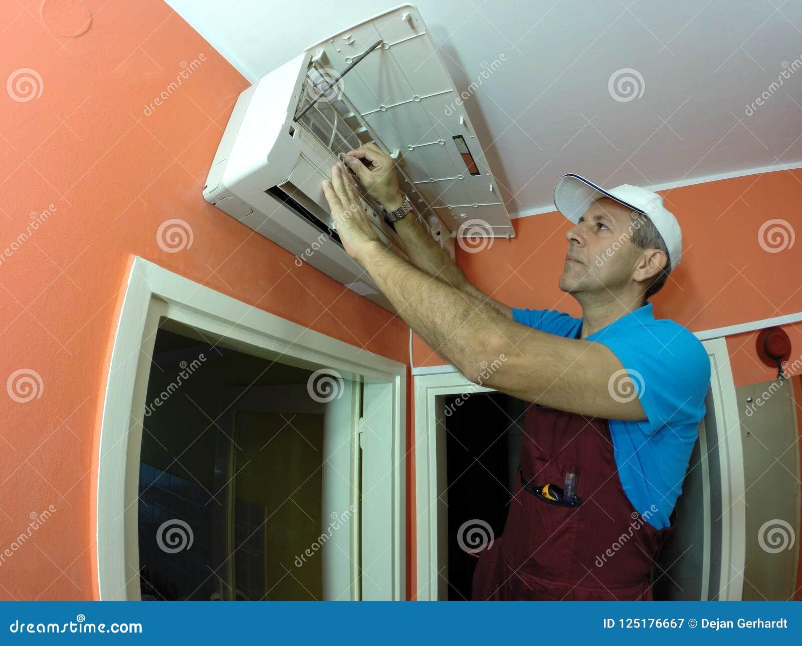 Tekniker Remove And Clean filtret av luft Conditione