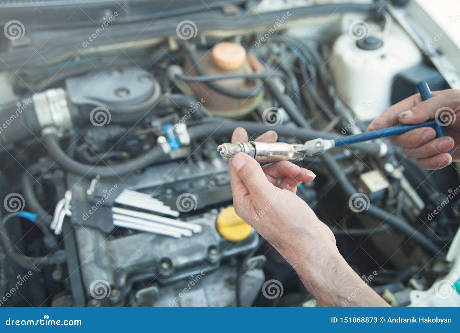 Tekniker som installerar den nya stearinljuset i bilmotor