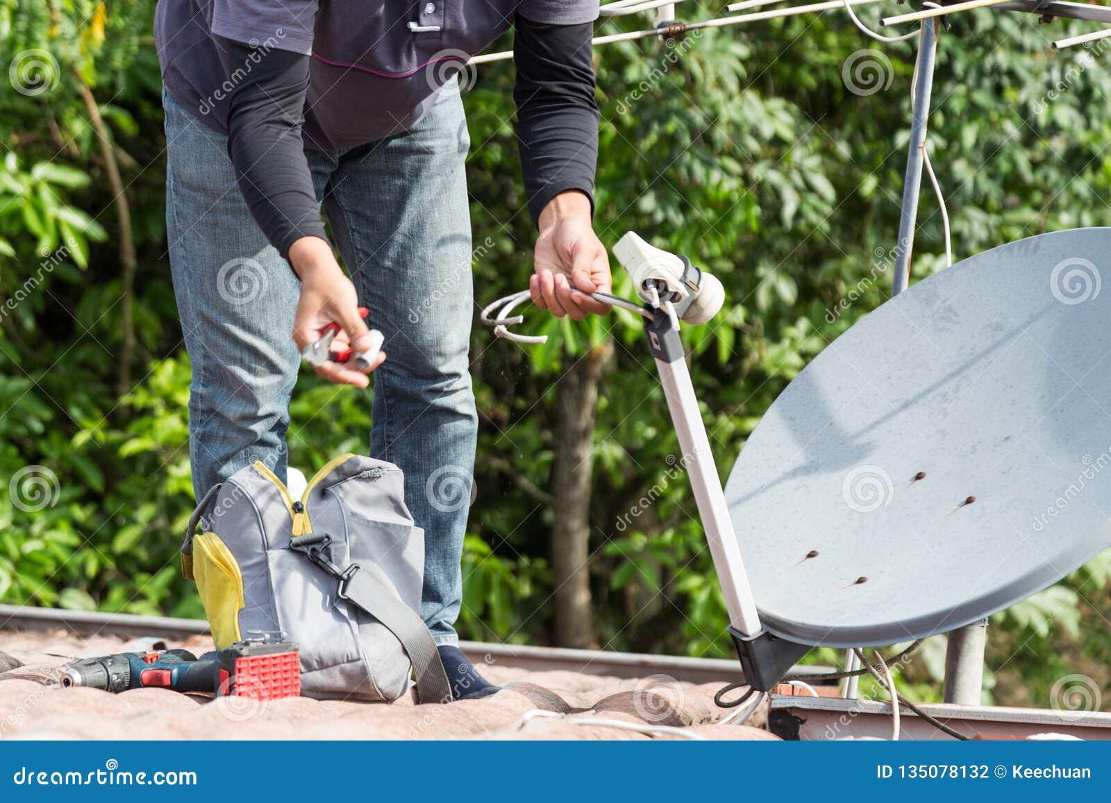 Tekniker som installerar den satellit- maträtten och televisionantennen på taköverkant