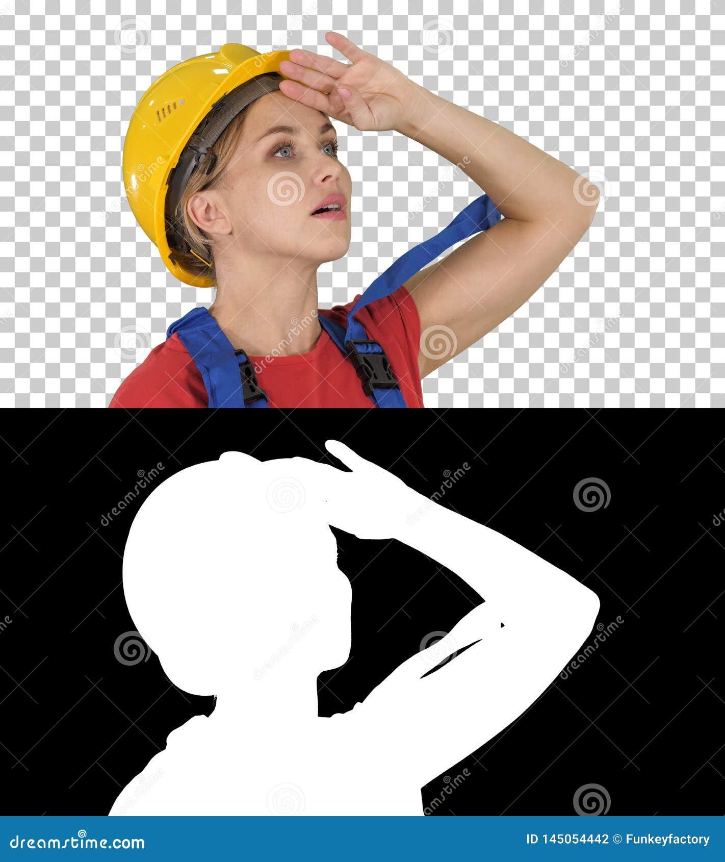 Teknikerbyggnadsarbetarekvinna som fascineras av skalan av konstruktion, alfabetisk kanal