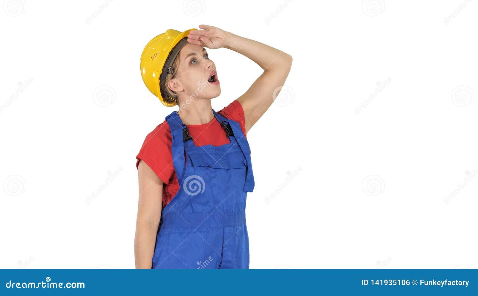 Teknikerbyggnadsarbetarekvinna som ser upp förbluffad på vit bakgrund