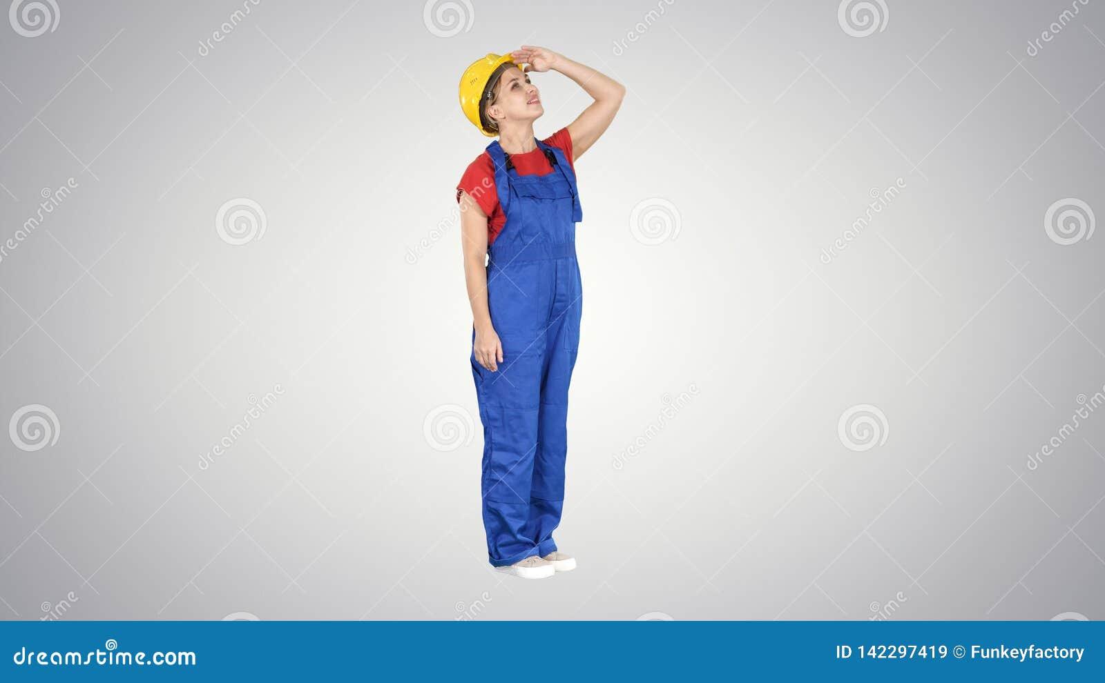 Teknikerbyggnadsarbetarekvinna som ser upp på en byggnad eller statistik eller graf som slutligen skrattar på lutning