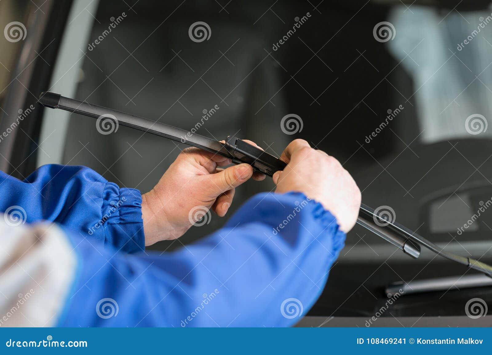 Teknikeren ändrar vindrutatorkare på en bilstation