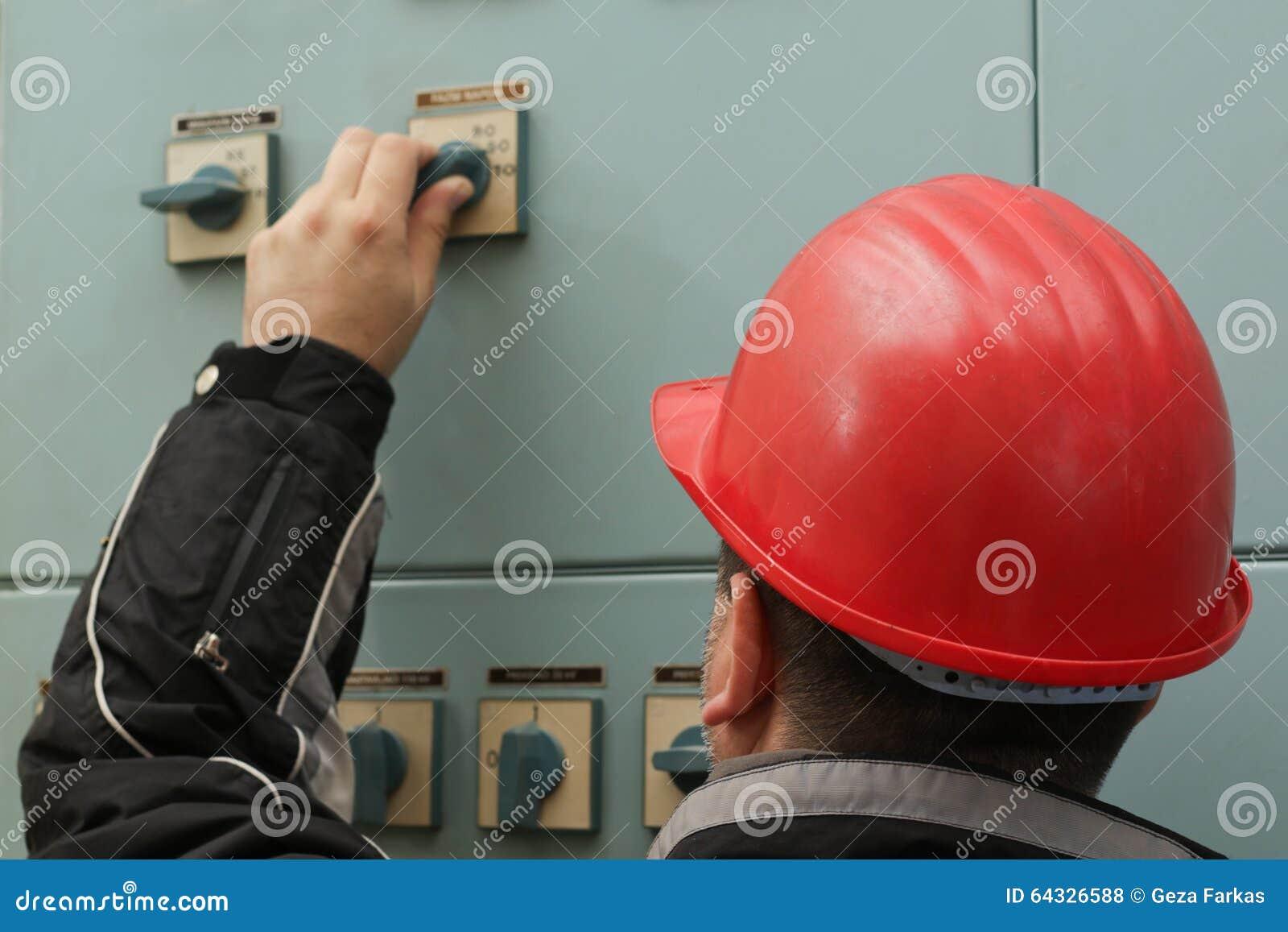 Teknikeren med den röda hjälmen vänder av maktströmbrytaren