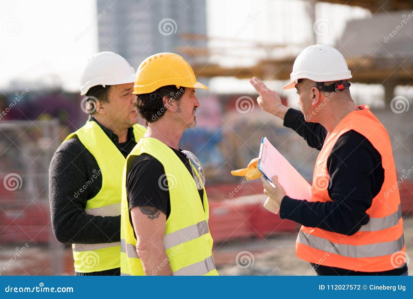Teknikerer och byggnadsarbetare på arbete
