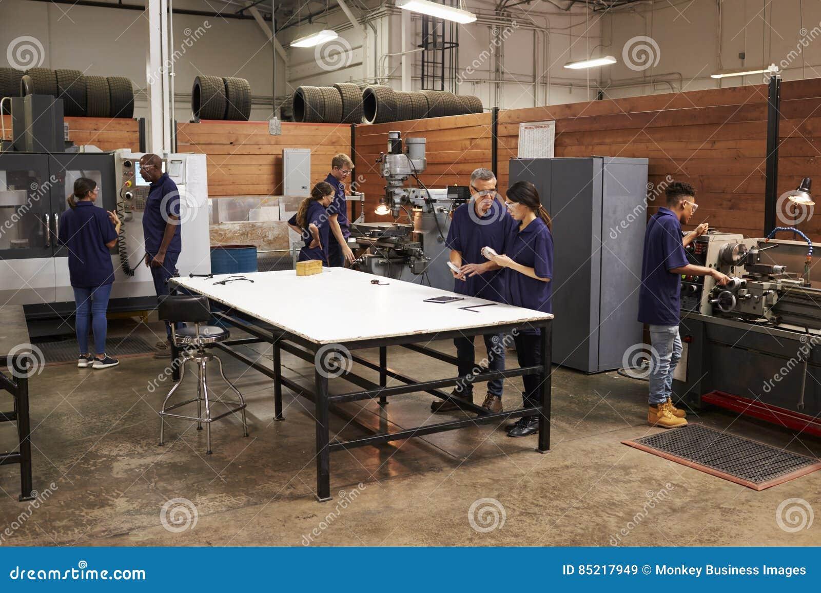 Teknikerer som arbetar på maskiner i upptaget metallseminarium