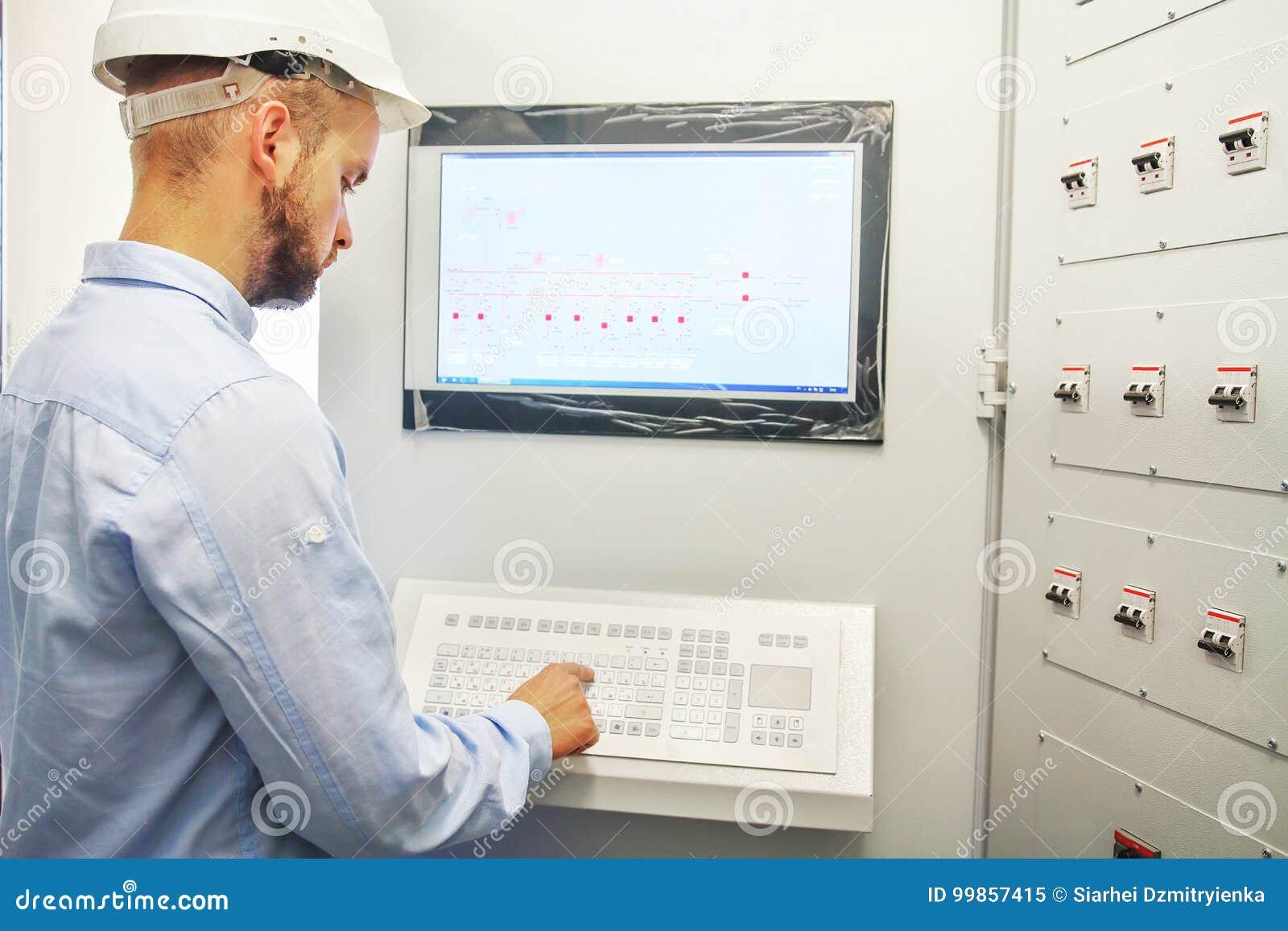 Teknikern kontrollerar teknologisk utrustning från fjärrkontrollbräde Scada system för automationutrustning