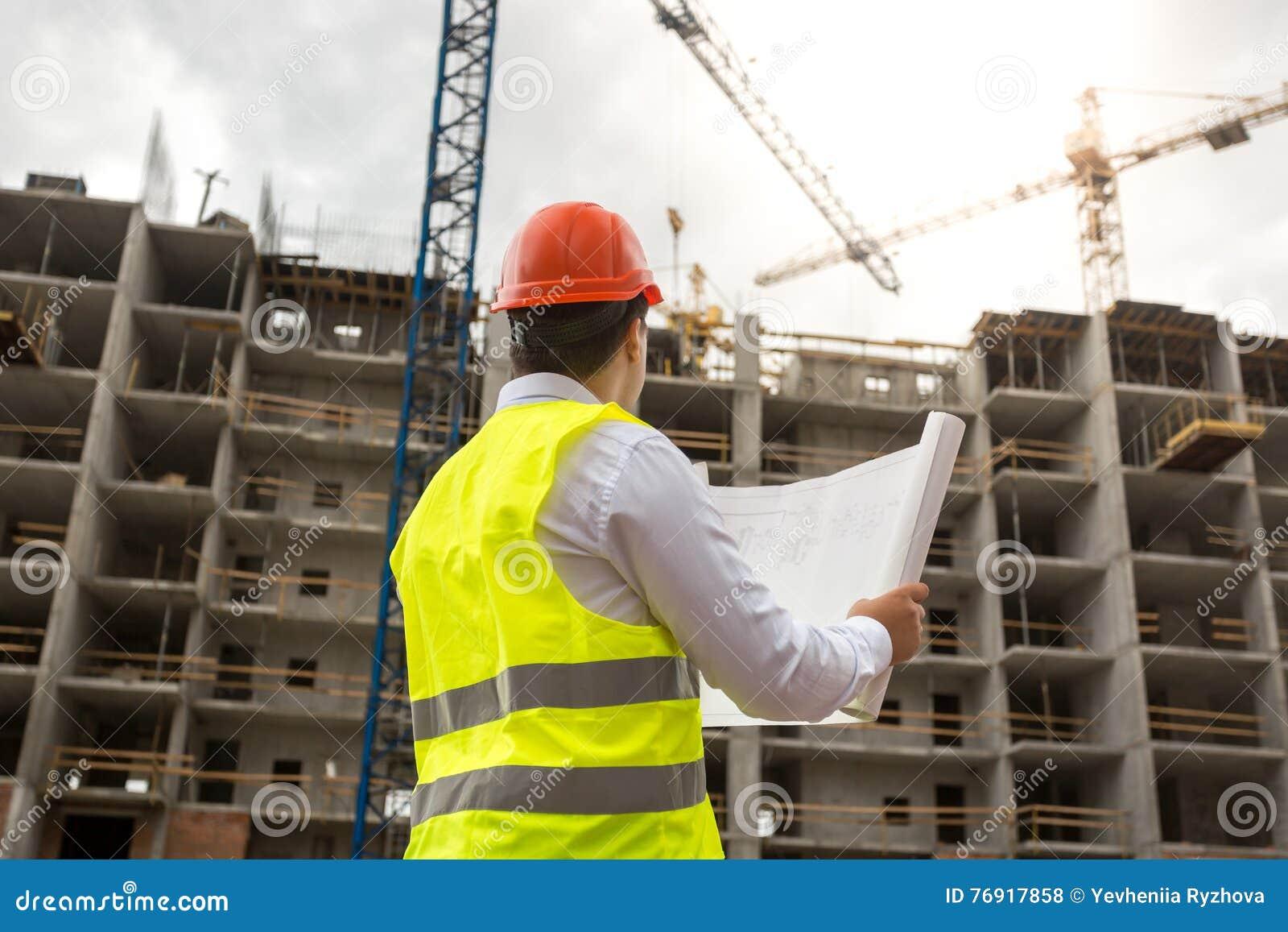 Teknikern på byggnadsplats undersöker ritningar