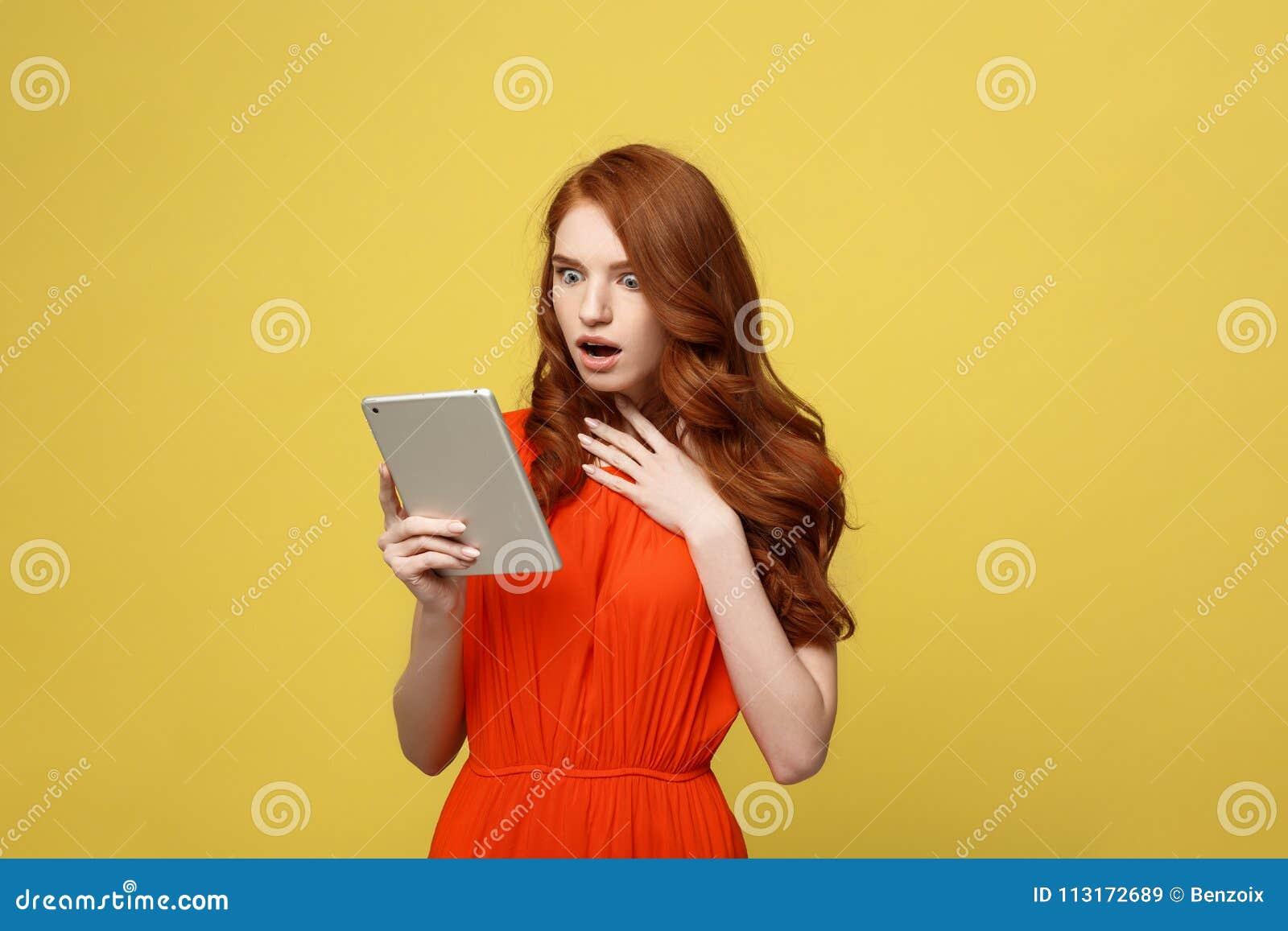Teknologi- och livsstilbegrepp: Den förvånade unga kvinnan som bär den orange klänningen beklär genom att använda minnestavlaPC s