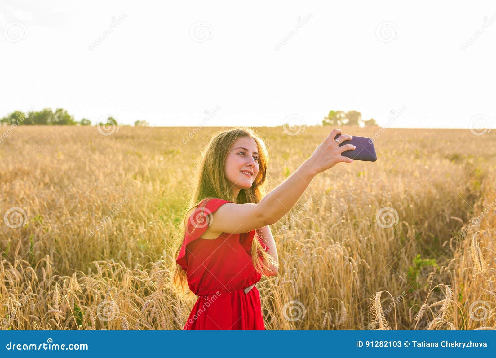Teknologi, sommarferier, semester och folkbegrepp - le den unga kvinnan som tar selfie vid smartphonen på sädesslag