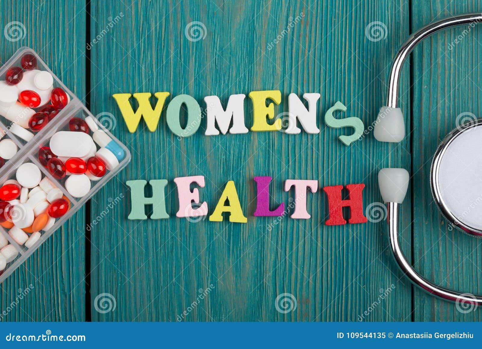 Tekst & x22; Women& x27; s health& x22; van gekleurde houten brieven, stethoscoop en pillen