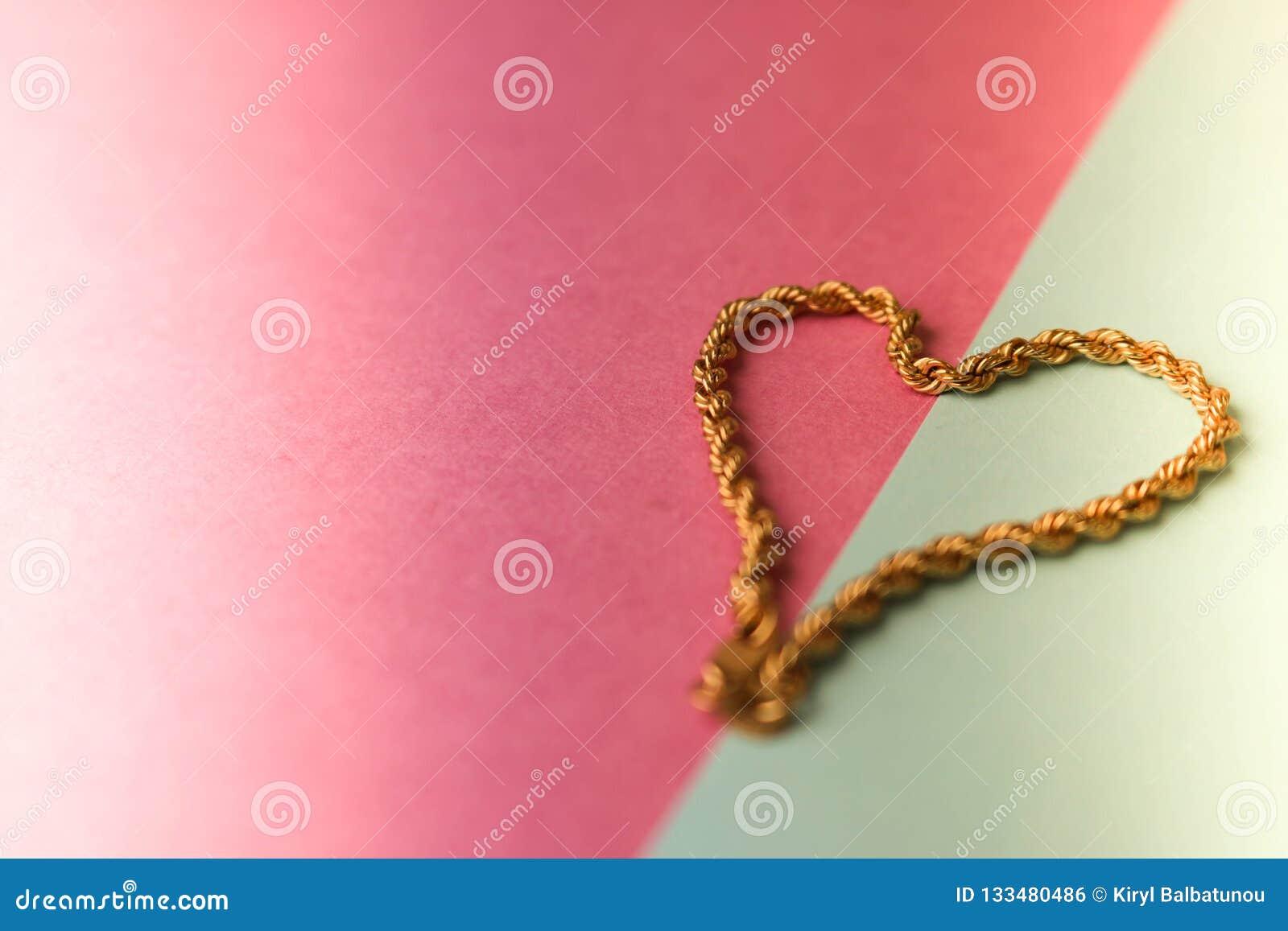 Tekstura piękny złoty świąteczny łańcuszkowy unikalny tkactwo w formie serca na różowej purpurowej błękitnej tła i kopii przestrz