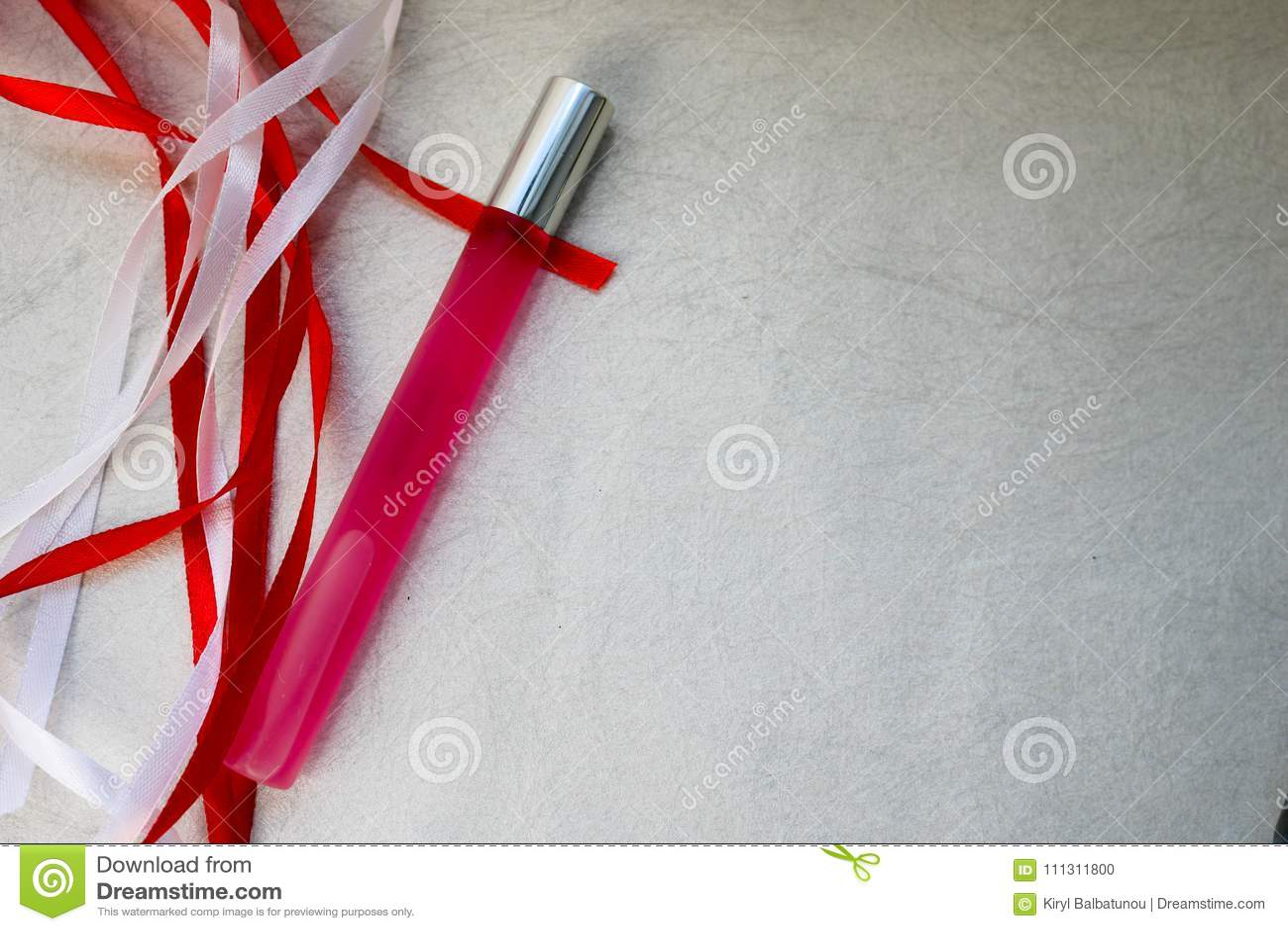 Tekstura z różowego matte pachnidła cienką długą cylindryczną butelką, cologne z czerwonymi i białymi pięknymi świątecznymi fabor