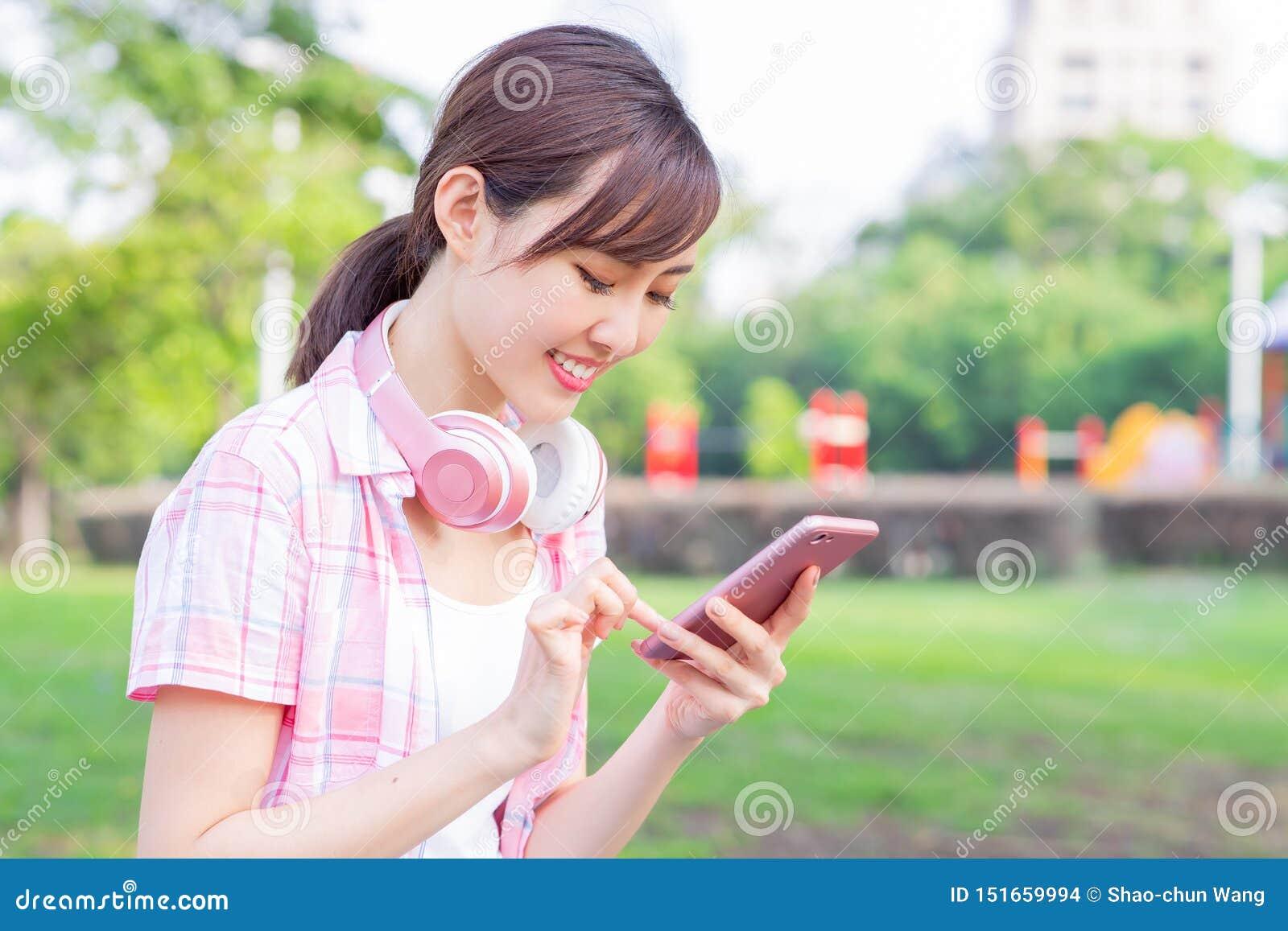 Teléfono asiático joven del uso de la mujer