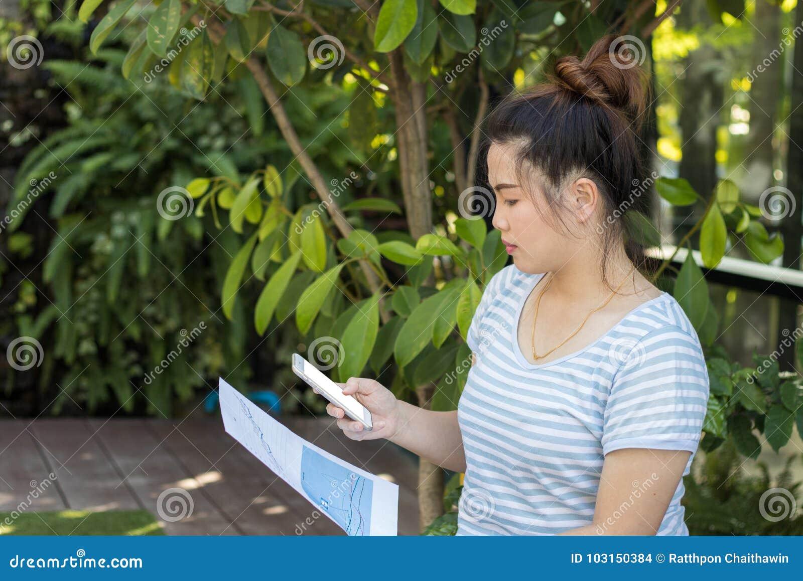 Teléfono del control asiático hermoso de la mujer del primer y papel elegantes de la tabla