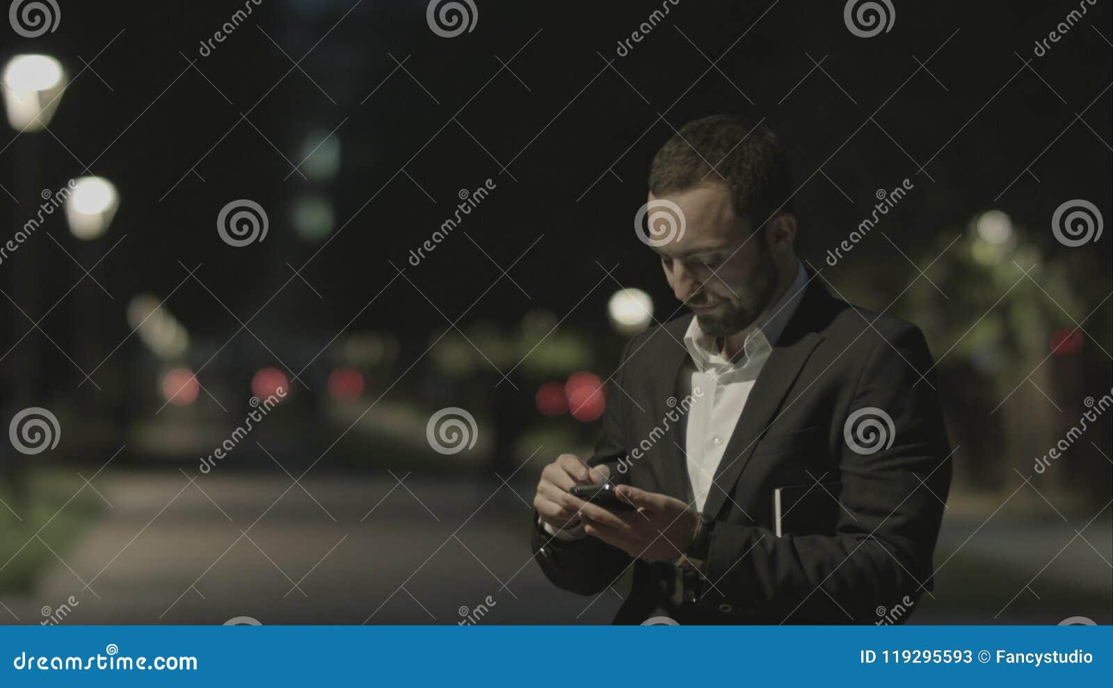 Teléfono elegante descontentado del uso barbudo del hombre de negocios, mientras que se coloca en la calle de la ciudad, mensajes