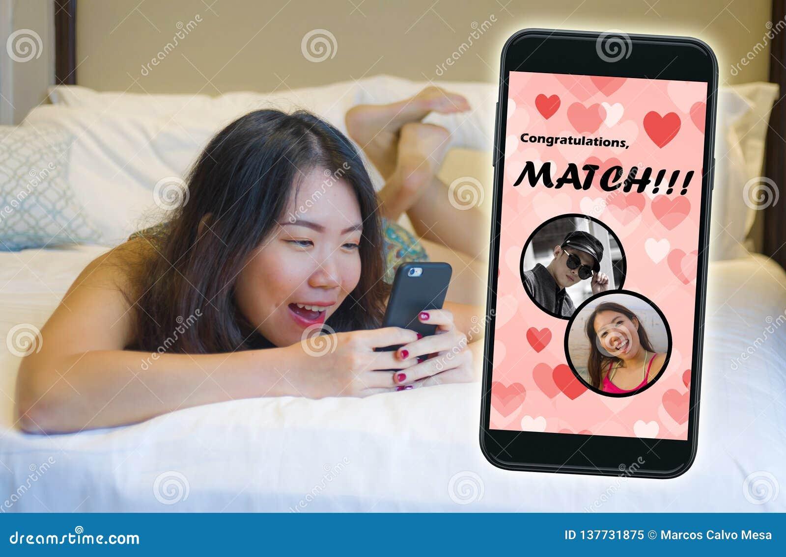 Teléfono móvil y muchacha china asiática hermosa y feliz joven que usa el app que fecha en línea alegre recibiendo un partido con