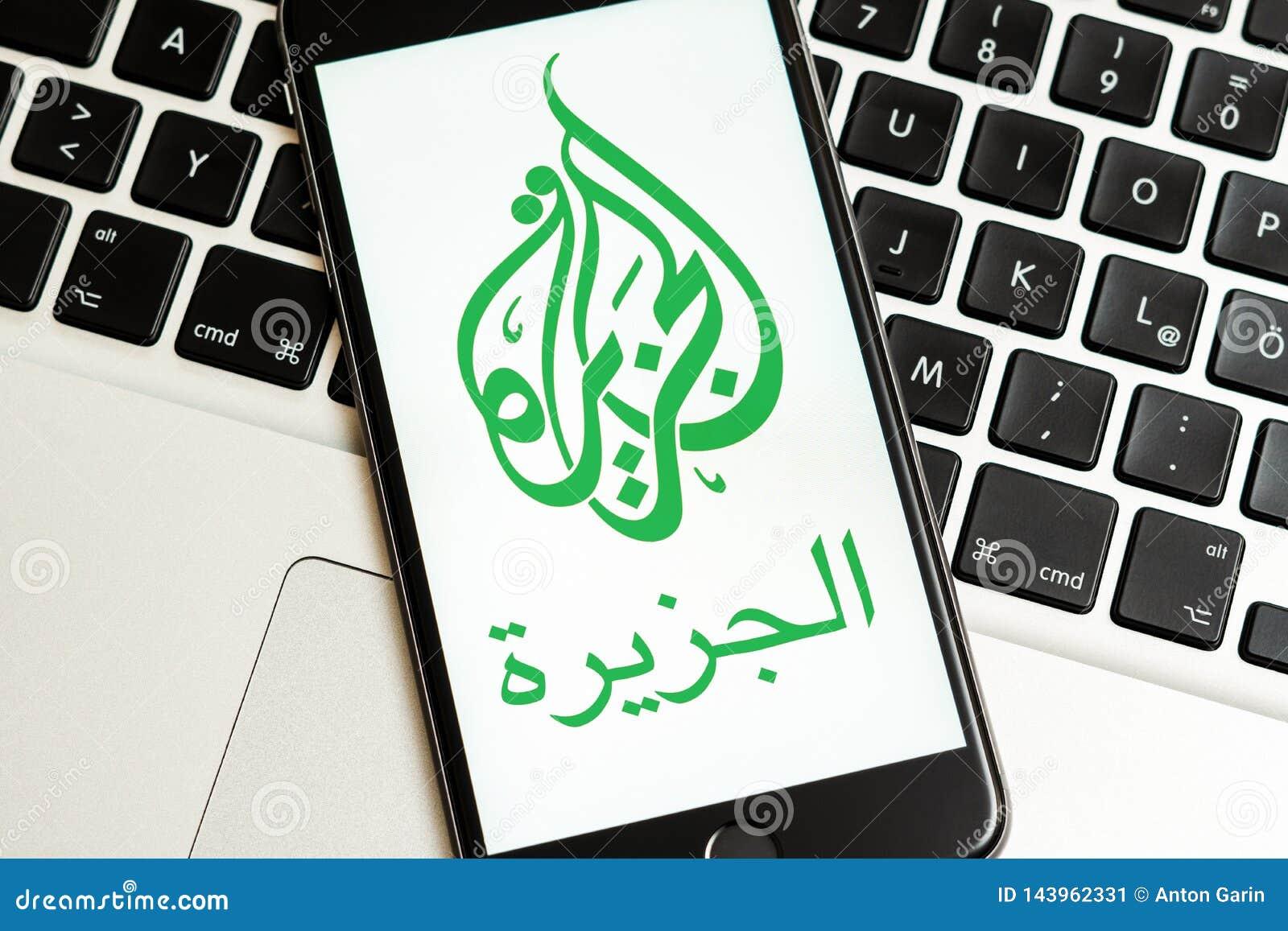 Teléfono negro con el logotipo de los medios de noticias Al Jazeera en la pantalla