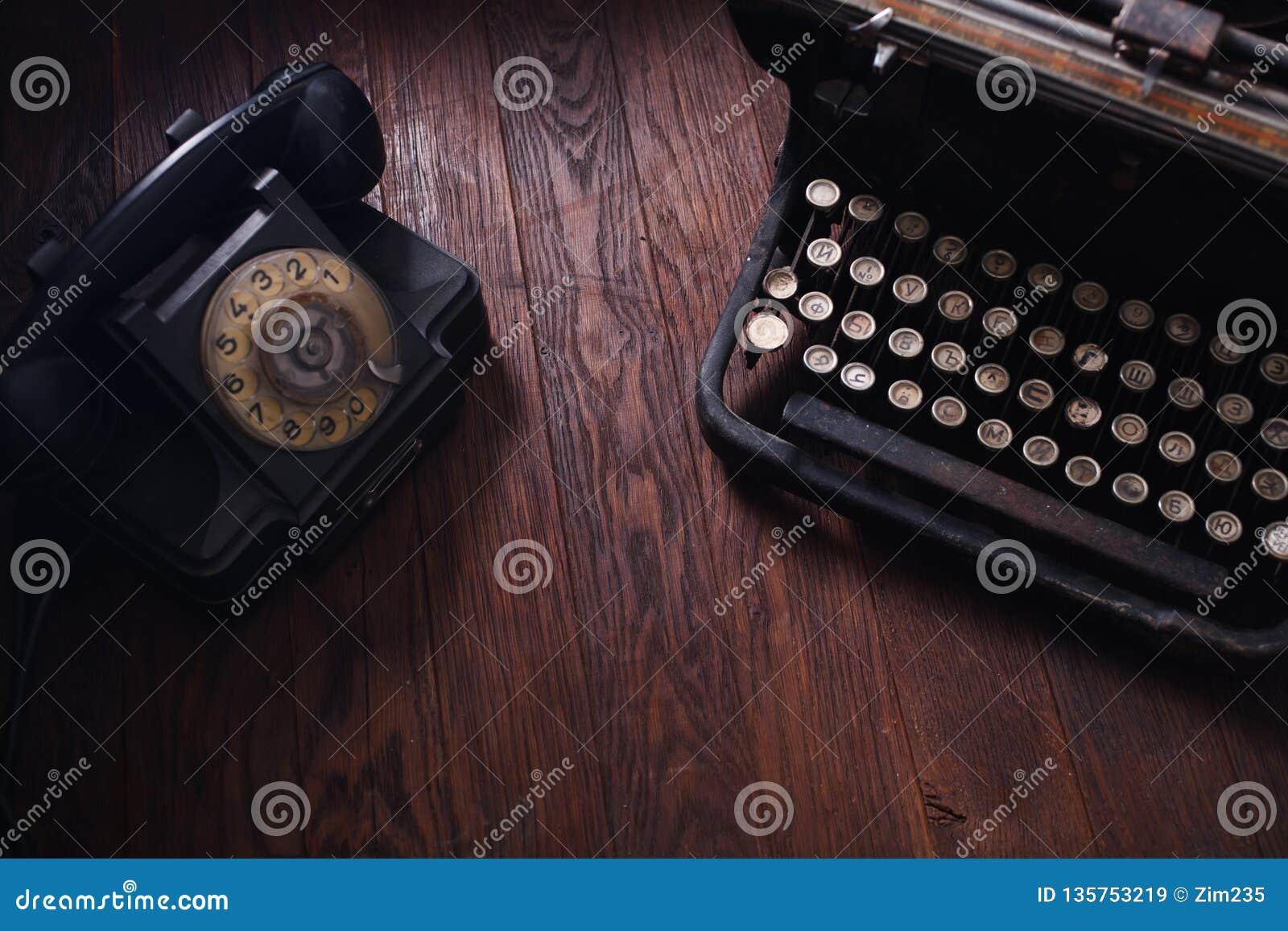 Teléfono retro viejo con la máquina de escribir del vintage en el tablero de madera